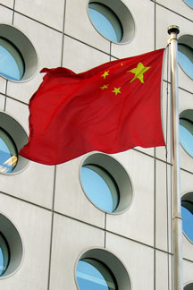 China flag with office building windows in the background